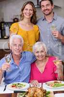 Portrait of a two generation family holding a wine glass at tabl
