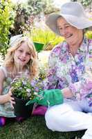 Grandmother and granddaughter holding a flower pot