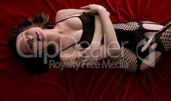 Top view of model posing in black fishnet bodysuit