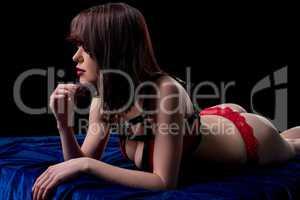 Erotica. Studio photo of brunette leaning on bed