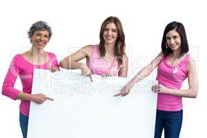 Women in pink outfits holding board for breast cancer awareness