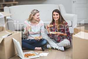 Two beautiful woman having pizza in the new house