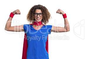 Portrait of smiling woman in superhero costume while flexing mus