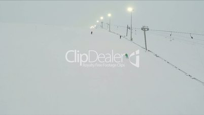 Chair Lifts And Skiers On Slope