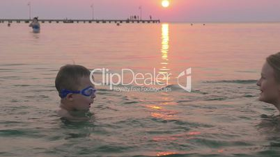 Boy in goggles learning to swim with his mother