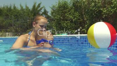 Mother and son in swimming pool. Son learning to swim.