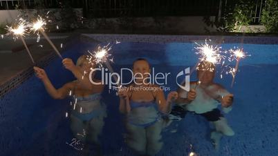Celebration with sparklers in the swimming pool