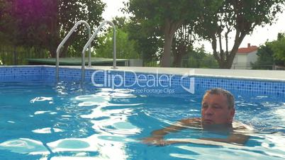Mature man relaxing with swimming in the pool