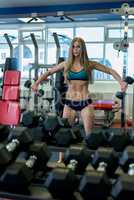 Sexy girl exercising with dumbbells at gym