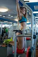 At gym. Beautiful girl pulls up on horizontal bar