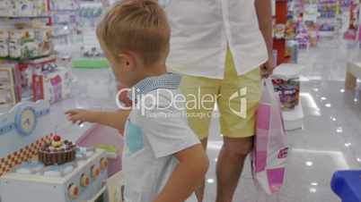 Child is attracted with toy cooker in supermarket