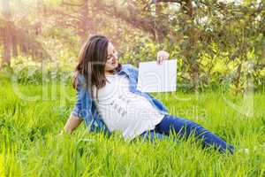 Pregnant woman outdoor with a paper in hand