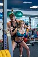 Coach insures girl while she squats with barbell