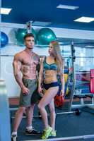 In gym. Image of pretty girl looks at bodybuilder