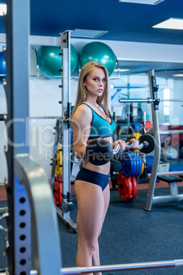 In gym. Sexy girl posing while holding dumbbell