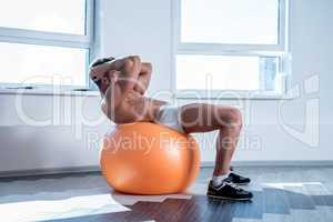 In gym. Bodybuilder doing push-ups on fitness ball