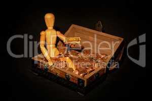 Holzfigur sitzt in Holzkiste mit Geld
