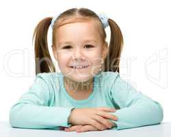Happy little girl sits at a table and smile
