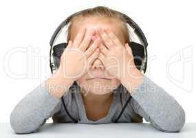 Unhappy girl listening music using headphones