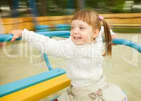 Cute little girl is riding merry-go-round