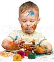 Little boy is playing with paints