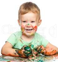 Child is grabbing some paint using fingers