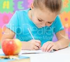Little girl is writing using a pen