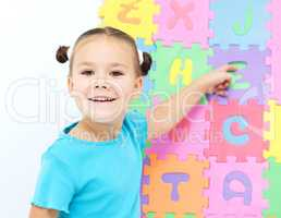 Little girl is pointing at letter Z on alphabet