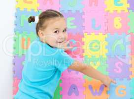 Little girl is pointing at letter G on alphabet