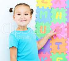 Little girl is pointing at letter O on alphabet