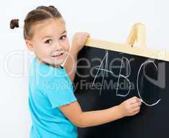 Little girl is showing letter E on the alphabet