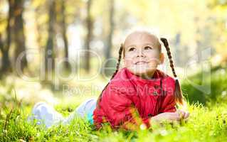 Cute little girl is playing with leaves in park