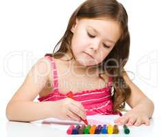 Little girl is drawing using a crayons