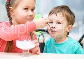 Girl is feeding his little brother with ice-cream