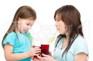 Mother and her daughter are drinking juice