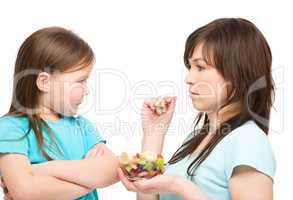 Mother is trying to feed her daughter