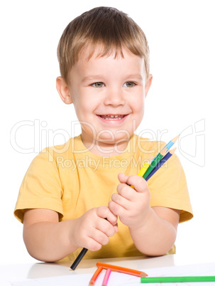 Little boy is playing with color pencils