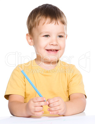 Little boy is drawing using color pencils