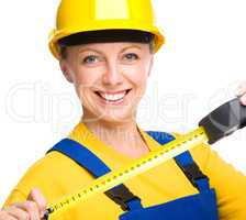 Young construction worker with tape measure