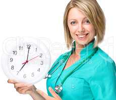 Young lady doctor is holding clock showing seven