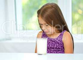Sad little girl with a glass of milk