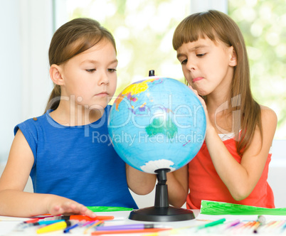 Little girls are examining globe