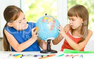 Little girls are examining globe