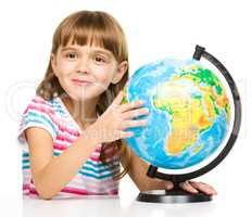 Little girl is examining globe