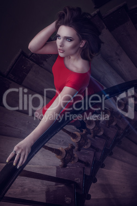 pretty woman wearing red dress on old stairs