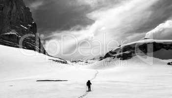Hiker on snow plateau. Black and white panoramic view.