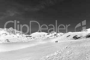 Two hikers on snow plateau (black and white)