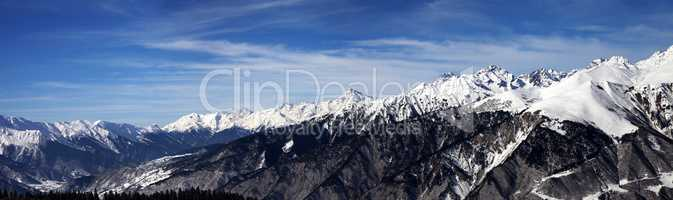 Panoramic view on snowy mountains in sun windy day