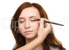 Stylist is applying eyeshadow for young girl