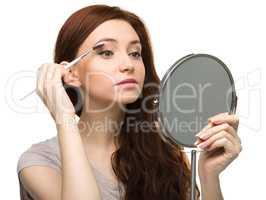 Young woman is applying eyeshadow